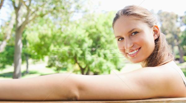 Oldalnézet mosolyog fiatal nő ül park pad Stock fotó © wavebreak_media
