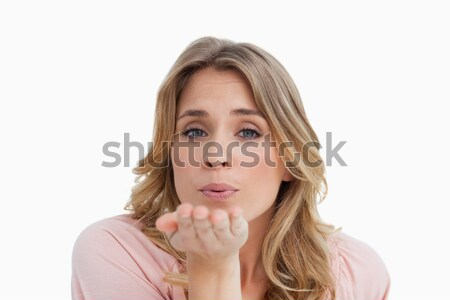 Young blonde woman blowing while sending an air kiss against a white background Stock photo © wavebreak_media