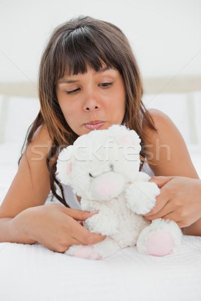Jonge vrouw spelen teddybeer bed witte slaapkamer Stockfoto © wavebreak_media