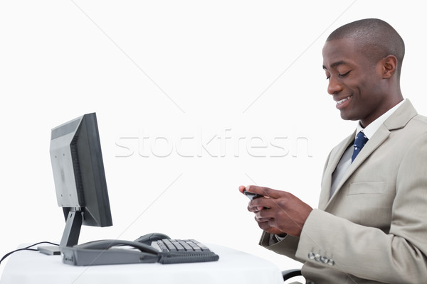 Side view of a smiling businessman sending a text message against a white background Stock photo © wavebreak_media