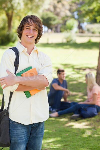 Uśmiechnięty młody człowiek stwarzające podręcznik parku znajomych Zdjęcia stock © wavebreak_media