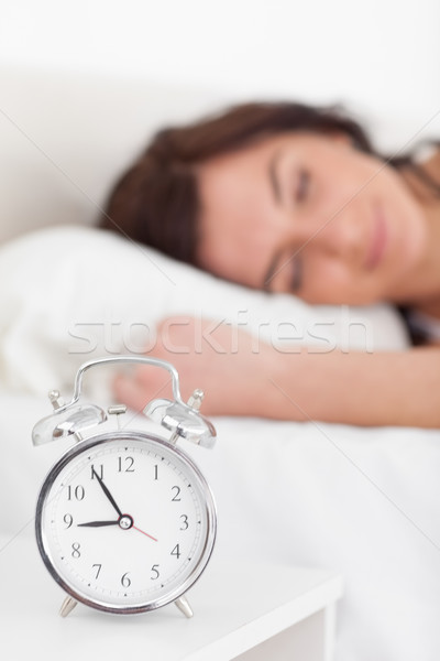 Alarm clock being placed on a nightstand in a bedroom Stock photo © wavebreak_media