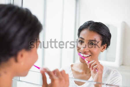 Doctor is looking into the mouth of the woman with in instrument and smiles Stock photo © wavebreak_media