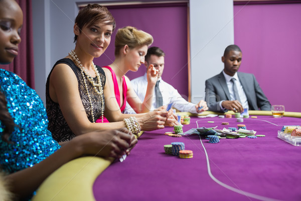 Stock photo: People sitting at the table of the casino smiling holding cards