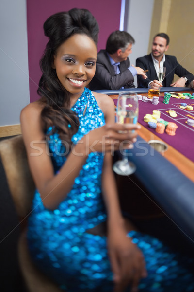 Woman at roulette table holding champagne glass in casino Stock photo © wavebreak_media