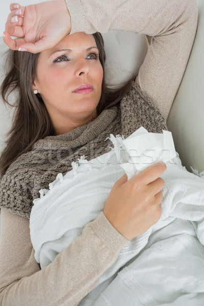 Ill woman lying on sofa with blanket holding a tissue feeling sorry for herself Stock photo © wavebreak_media
