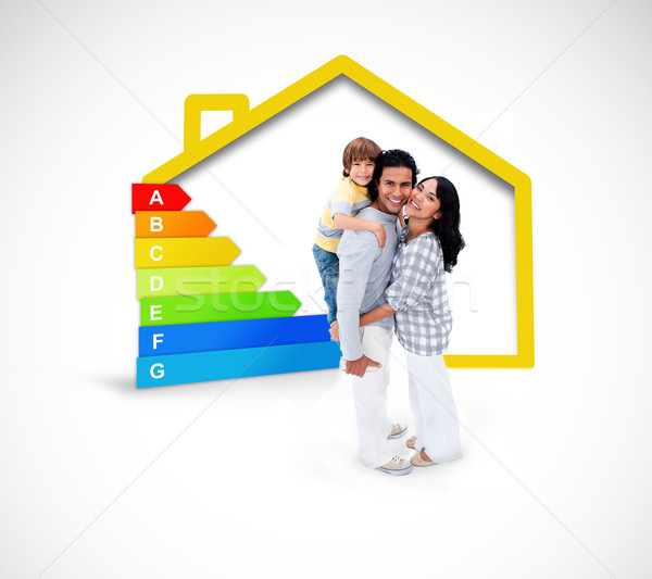 Smiling family standing with a yellow house illustration with energy rating Stock photo © wavebreak_media