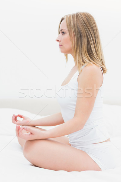Side view of woman sitting in lotus position in bed Stock photo © wavebreak_media