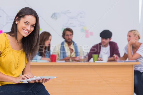 Stock photo: Prettty editor using tablet as team works behind her