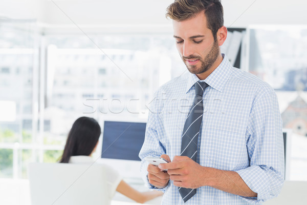 Casual male artist text messaging with colleague in background Stock photo © wavebreak_media