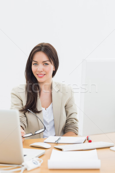 Well dressed woman with laptop at desk in office Stock photo © wavebreak_media