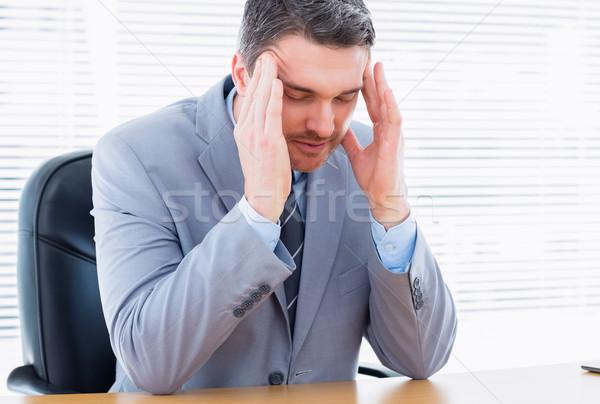 Businessman with severe headache sitting at office desk Stock photo © wavebreak_media