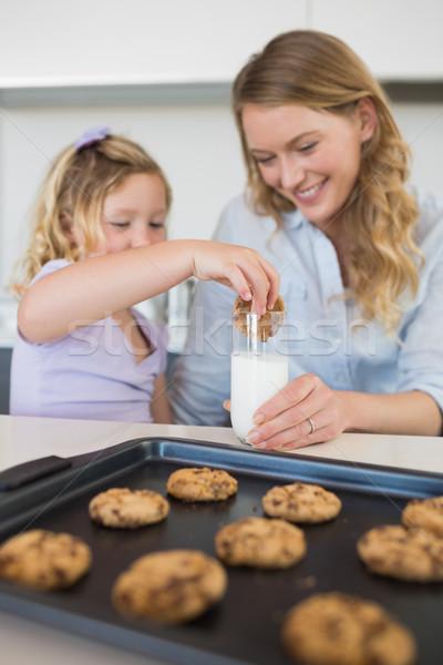 Mother with daughter dipping cookie in milk Stock photo © wavebreak_media