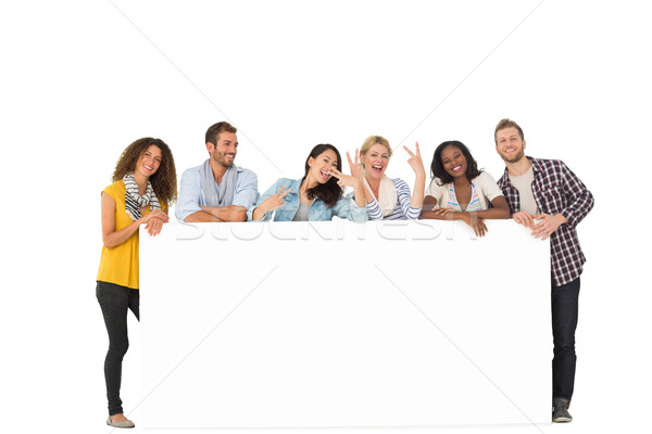 Happy group of young friends leaning on large poster Stock photo © wavebreak_media