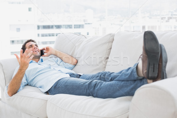 Smiling man lying on the couch talking on the phone Stock photo © wavebreak_media