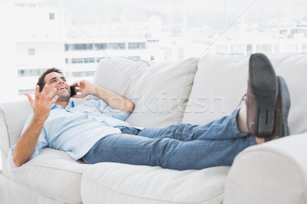 улыбаясь человека диване говорить телефон домой Сток-фото © wavebreak_media