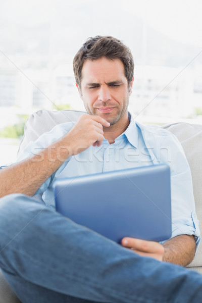 Thinking man sitting on the couch using his tablet Stock photo © wavebreak_media