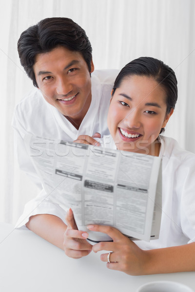 Couple in bathrobes reading newspaper together in the morning Stock photo © wavebreak_media