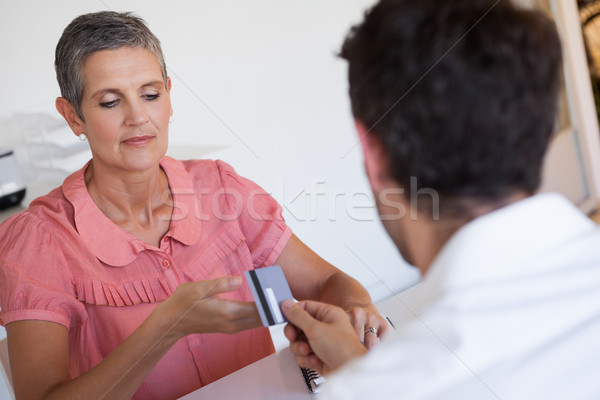 Casual saleswoman taking credit card from customer Stock photo © wavebreak_media