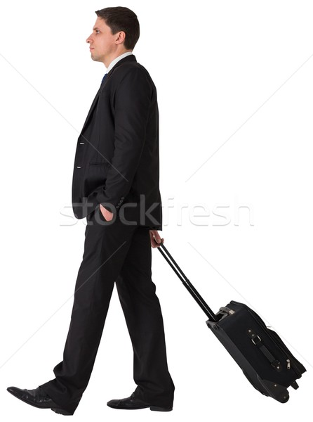 Handsome businessman pulling his suitcase Stock photo © wavebreak_media