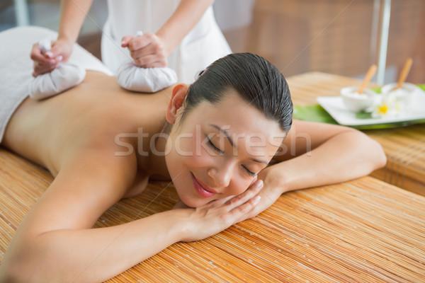 Smiling brunette getting a herbal compress massage Stock photo © wavebreak_media