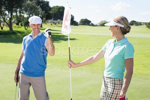 Lady golfer holding eighteenth hole flag for cheering partner Stock photo © wavebreak_media