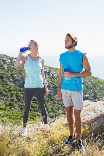 Fit couple standing drinking from water bottles Stock photo © wavebreak_media