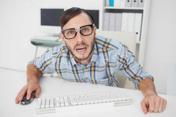 Stock photo: Nerdy stressed businessman working on computer