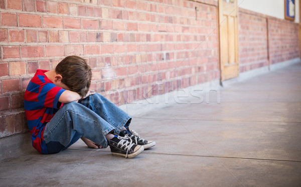 Stock photo: Sad pupil sitting alone in corridor
