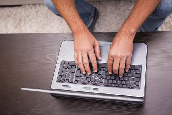 Homem usando laptop mesa de café casa sala de estar computador Foto stock © wavebreak_media