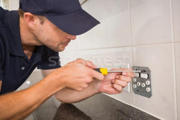 Electrician unscrewing face plate of plug socket Stock photo © wavebreak_media