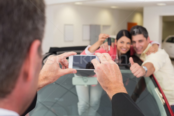 Businessman taking picture of the couple in their new car Stock photo © wavebreak_media