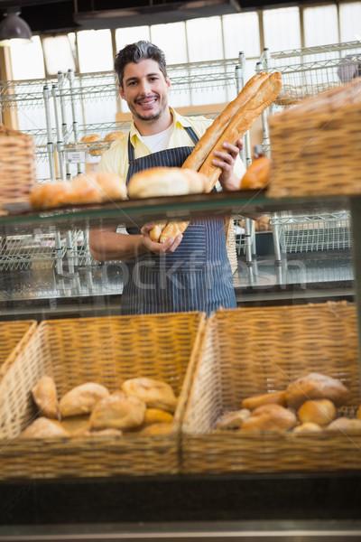 Smiling waiter holding two baguettes  Stock photo © wavebreak_media