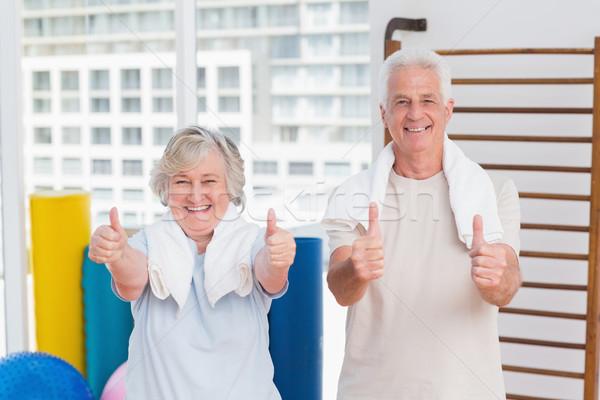 Senior couple gesturing thumbs up in gym Stock photo © wavebreak_media