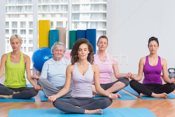 Class with instructor in lotus position at gym Stock photo © wavebreak_media