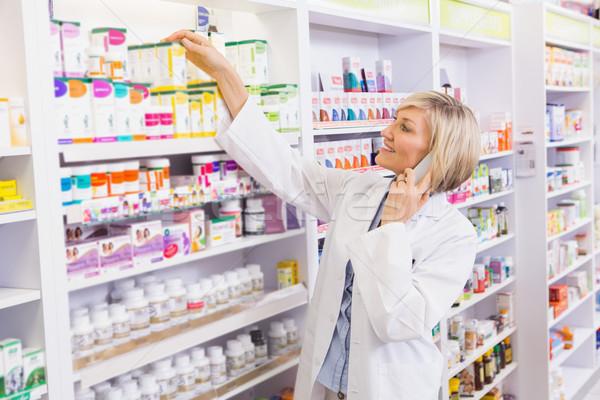 Smiling pharmacist phoning and taking medicine from shelf Stock photo © wavebreak_media