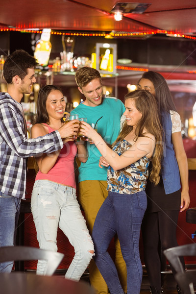 Smiling friends drinking beer and mixed drink Stock photo © wavebreak_media