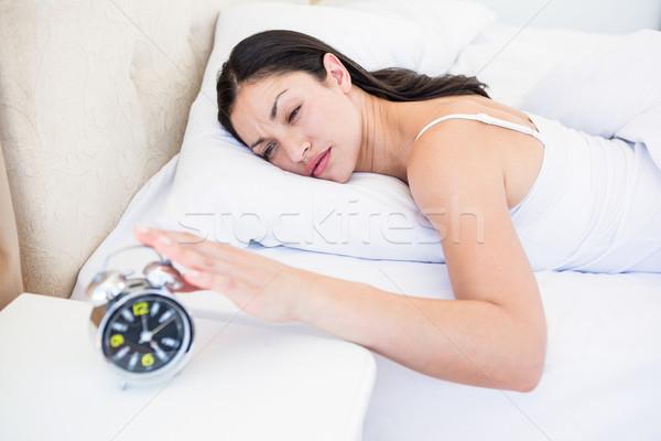 Pretty brunette turning off alarm clock on bed  Stock photo © wavebreak_media