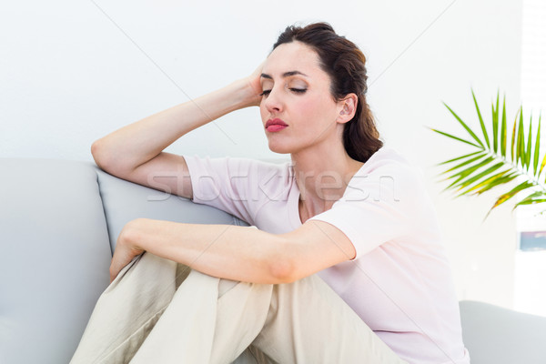Sad brunette sitting on the couch Stock photo © wavebreak_media