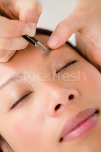 Woman using tweezers on patient eyebrow Stock photo © wavebreak_media