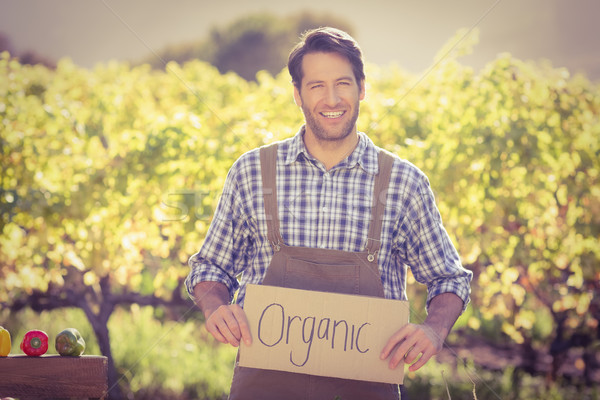 Smiling farmer holding an organic sign Stock photo © wavebreak_media