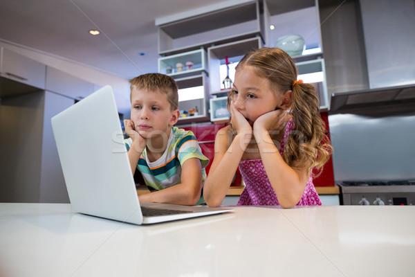 Siblings using laptop in kitchen Stock photo © wavebreak_media