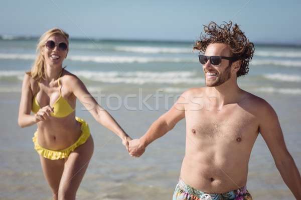 Happy couple holding hands while running at beach Stock photo © wavebreak_media