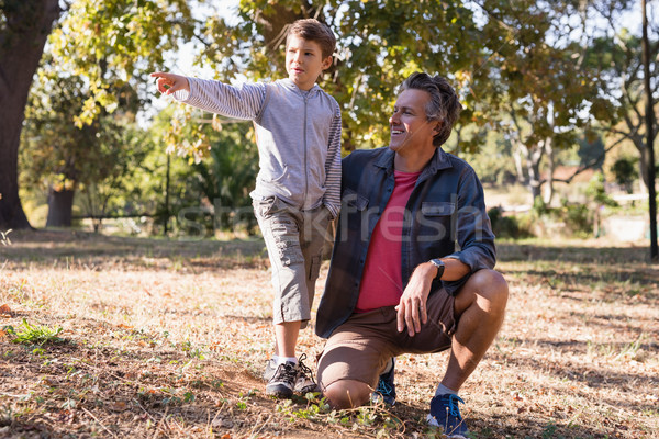 Happy man looking at boy pointing away in forest Stock photo © wavebreak_media