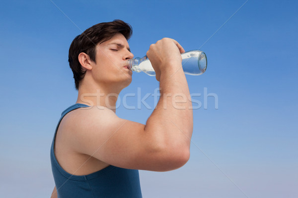 Man drinking water from bottle at beach Stock photo © wavebreak_media