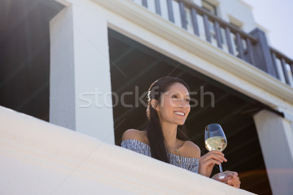 Smiling young woman holding white wine glass in balcony at restaurant Stock photo © wavebreak_media
