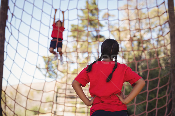 Girl looking at her friend while climbing net during obstacle course Stock photo © wavebreak_media