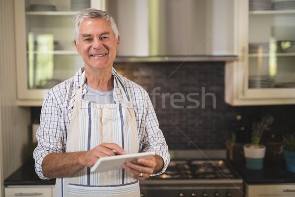 Smiling senior man using digital tablet in kitchen at home Stock photo © wavebreak_media
