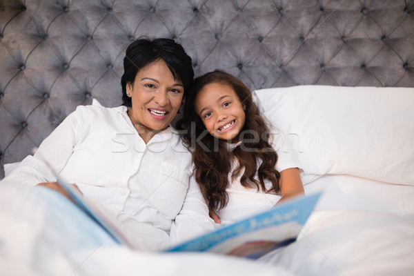 Portrait of happy grandmother and granddaughter reading book on bed Stock photo © wavebreak_media