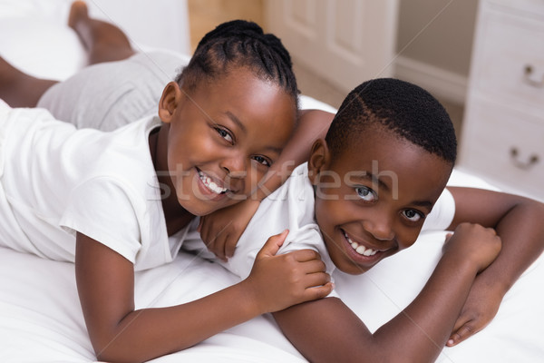 Portrait of smiling siblings lying on bed Stock photo © wavebreak_media